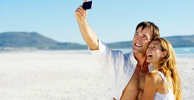 couple with a smartphone on the beach